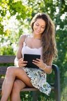 ragazza seduta su una panchina con ereader foto