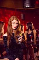 bella rossa che beve un cocktail foto