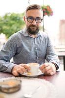 uomo elegante che beve caffè all'aperto