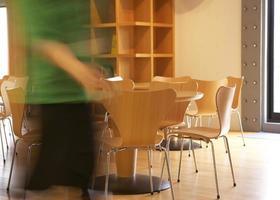 donna che cammina vicino a tavoli e sedie foto