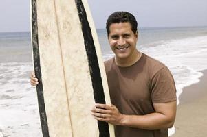 Ritratto di uomo che tiene la tavola da surf sulla spiaggia foto