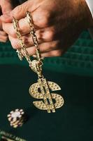 uomo che tiene una collana del segno del dollaro foto
