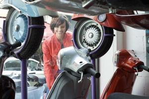 shopping finestra donna, guardando il display scooter, sorridendo foto