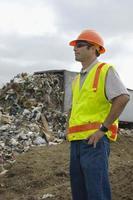 lavoratore in piedi vicino camion scarico rifiuti in discarica foto