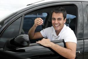 felice uomo ispanico nella sua nuova auto foto