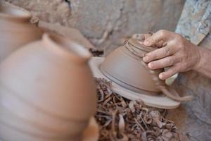 artigiano marocchino lancia una pentola di terracotta su un tornio da vasaio. foto