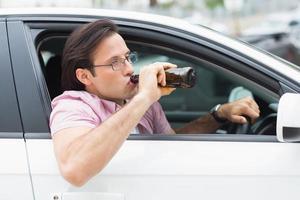 uomo che beve birra durante la guida foto