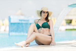 bella giovane donna a bordo piscina foto