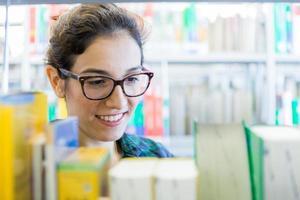 giovane studente alla ricerca di libri in biblioteca foto