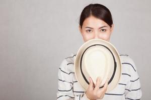 bella ragazza asiatica tenere un cappello chiudere la bocca foto
