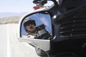 uomo di polizia che comunica sulla moto foto