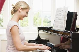 donna che suona il pianoforte e sorridente foto