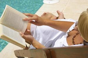 donna che legge un libro a bordo piscina.
