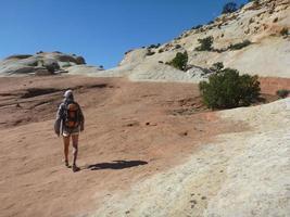 donna che fa un'escursione sul slickrock del deserto foto