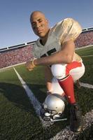 Ritratto del giocatore di football americano che si inginocchia sul campo foto