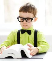 il ragazzino sta leggendo un libro foto