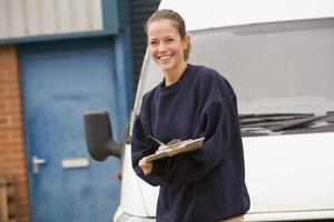 persona di consegna in piedi con van iscritto negli Appunti sorridente foto