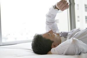 uomo d'affari che si trova sul letto guardando orologio