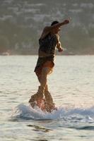 flyboarder torcendo la parte superiore del corpo appena sopra le onde foto