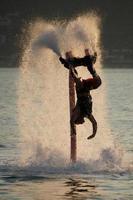 flyboarder che si tuffa in mezzo dello spruzzo dopo il rovescio della schiena foto
