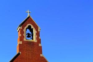 campanile contro il cielo blu foto