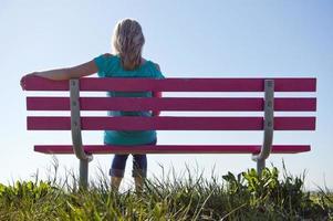 donna in blu, seduta su una panchina rosa in zona rurale
