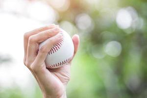 primo piano della mano del giocatore che tiene il baseball foto