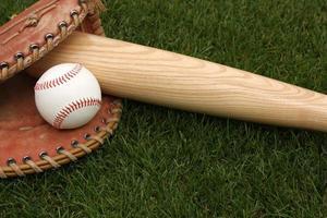 mazza da baseball, palla e guanto che giace nell'erba foto