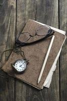 orologio da tasca, occhiali e vecchio taccuino sul tavolo foto