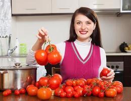 donna felice con pomodori rossi