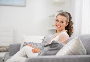 Ritratto di felice casalinga giovane seduto in salotto foto