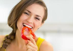 Ritratto di giovane donna felice che mangia peperone dolce in cucina