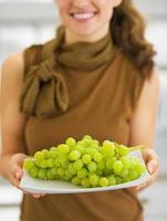 primo piano sul piatto con l'uva in mano della casalinga sorridente foto