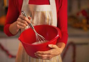 primo piano sulla giovane casalinga usando la frusta per pasta