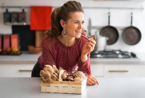 Ritratto di felice casalinga giovane con funghi in cucina