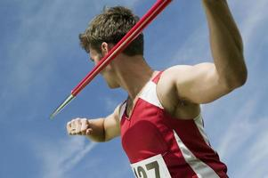 atleta maschio che tiene giavellotto foto