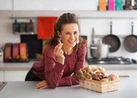 felice giovane casalinga con funghi in cucina foto