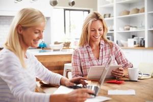 due donne che lavorano insieme a casa con il portatile foto