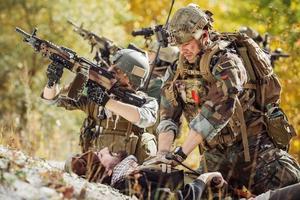 il soldato fornisce assistenza medica ai soldati afgani feriti foto