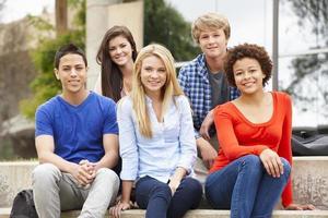 gruppo studentesco multietnico seduto all'aperto foto