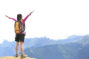 incoraggiante escursionismo donna picco di montagna foto