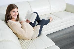 donna incinta allegra con romanzo foto