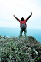 picco di montagna incoraggiante della viandante della donna escursionista foto