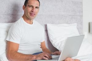 uomo allegro che per mezzo del computer portatile sul letto foto