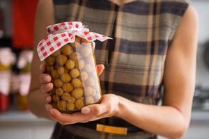 primo piano sulla casalinga che mostra barattolo con composta fatta in casa foto