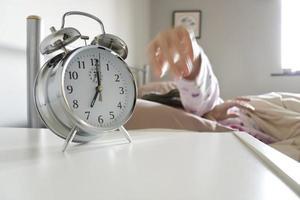 donna assonnata che raggiunge per spegnere la sveglia foto