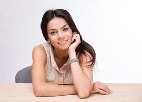 donna di affari allegra che si siede al tavolo foto
