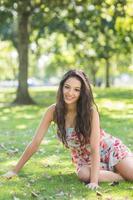 bruna allegra alla moda che si siede sull'erba