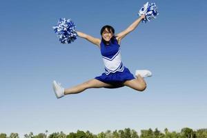 cheerleader esegue allegria a mezz'aria foto