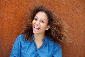 giovane donna allegra che sorride con i capelli ricci foto